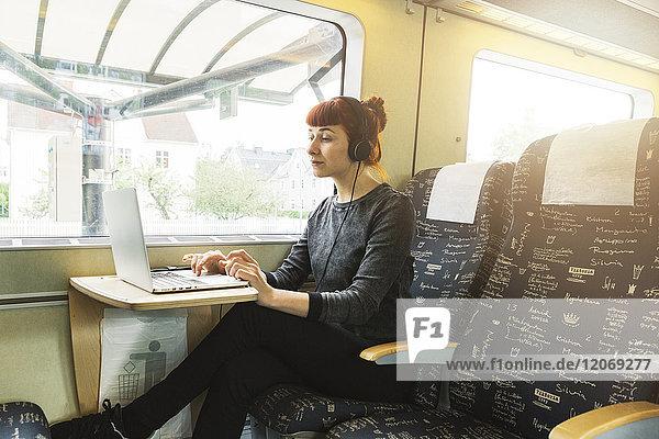 Frau mit Laptop im Zug