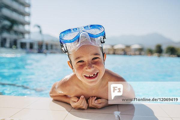 Ein glücklicher Junge  der sich an den Rand eines Pools lehnt.