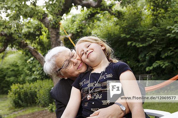 Großmutter und Enkelin umarmend