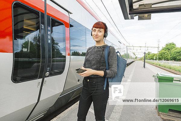 Frau mit Kopfhörer auf dem Bahnsteig
