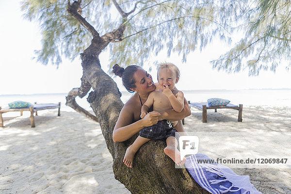 Kleinkind und seine Mutter sitzen auf einem Baum am Diani Beach  Kenia