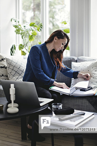 Businesswoman reading document while sitting on sofa at home office