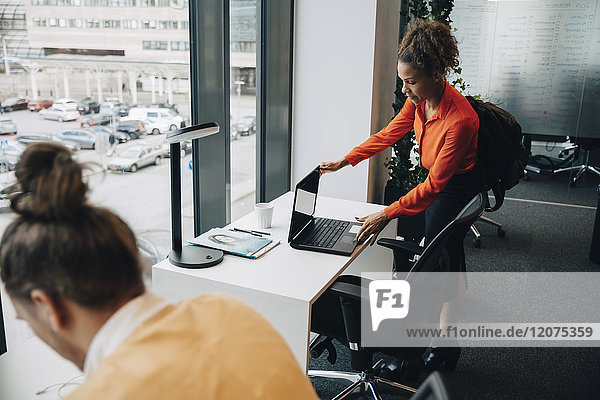 Businesswoman looking at laptop while male colleague working in office