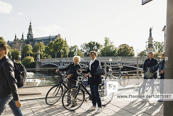 Full length of senior women with bicycles looking away while standing on sidewalk in city