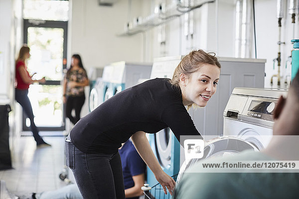 Smiling woman looking at friend while doing laundry