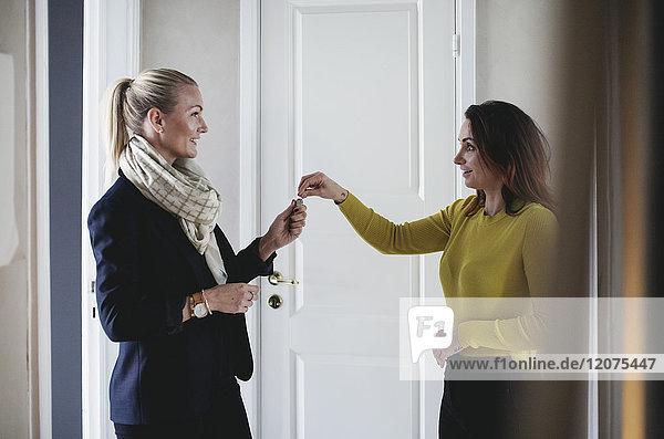 Lächelnde Geschäftsfrau übergibt Schlüssel an Kollegen zu Hause