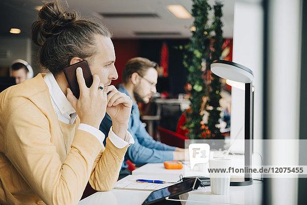 Seitenansicht eines mittelgroßen Geschäftsmannes  der auf einem Smartphone spricht  während er am Schreibtisch im Büro sitzt.