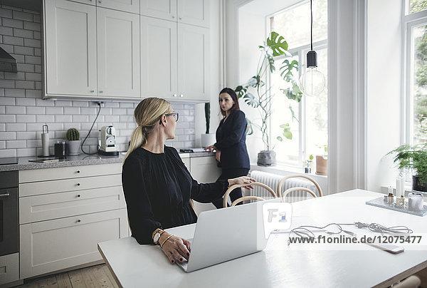 Geschäftsfrau im Gespräch mit Kollegen bei der Arbeit am Laptop im Home-Office