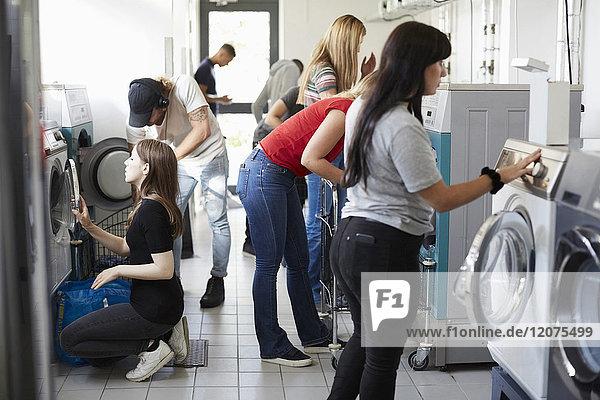 Multiethnische Universitätsstudenten beim Wäschewaschen im Waschsalon
