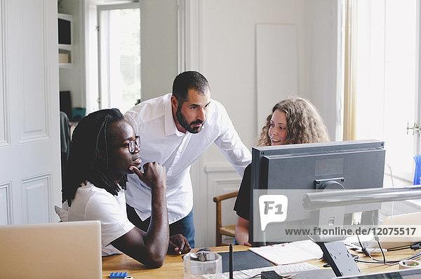 Geschäftsleute diskutieren über Computer am Tisch im Kreativbüro