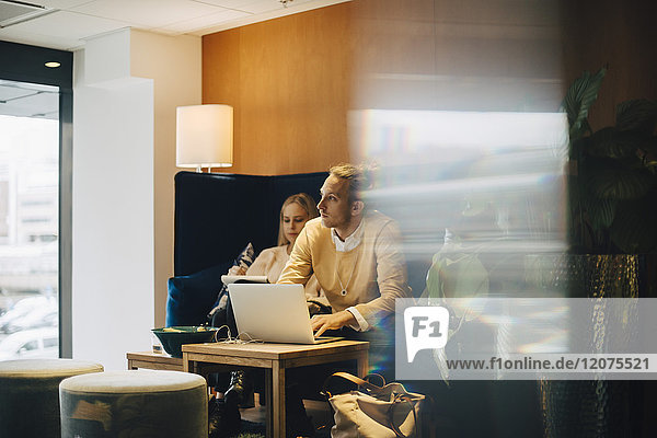 Geschäftsmann schaut weg  während er mit seinem Laptop in der Bürocafeteria sitzt.