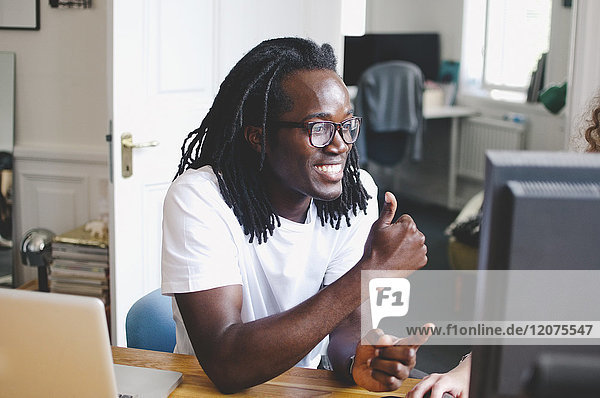 Smiling young businessman gesturing while sitting at table in creative office