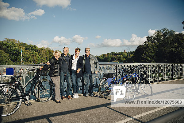 Volle Länge der älteren männlichen und weiblichen Freunde mit auf der Brücke stehenden Fahrrädern