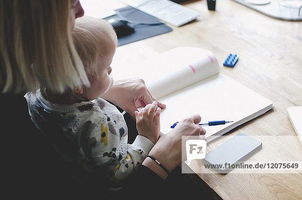 Hochwinkelansicht der Geschäftsfrau mit Baby Girl beim Tagebuchschreiben am Tisch im Kreativbüro