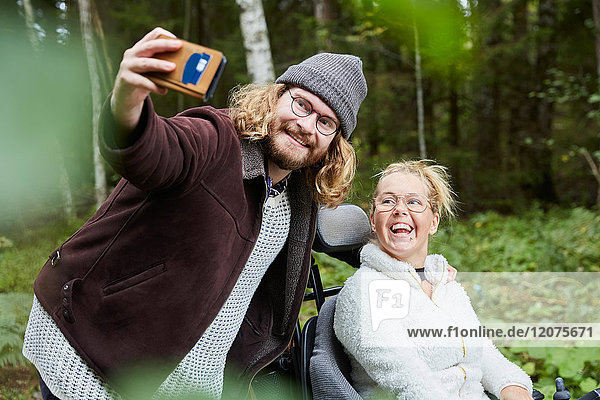 Junger männlicher Hausmeister  der sich mit einer behinderten Frau in den Wald begibt.
