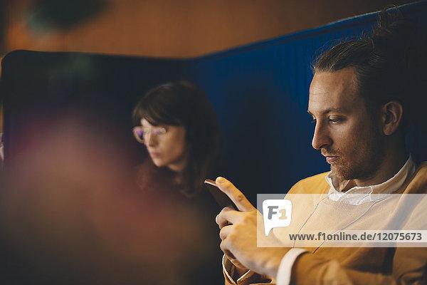 Mittlerer Erwachsener Geschäftsmann  der ein Smartphone benutzt  während er von einer jungen Kollegin in der Cafeteria sitzt.