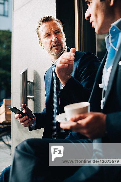 Geschäftsmann  der den männlichen Kollegen beim Kaffeetrinken im Cafe beobachtet.