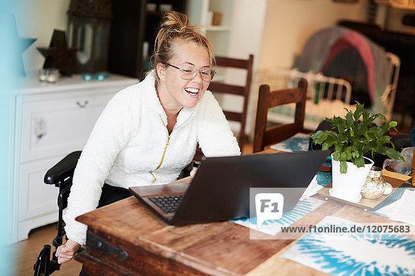 Lächelnde behinderte Frau mit Laptop am Tisch im Haus