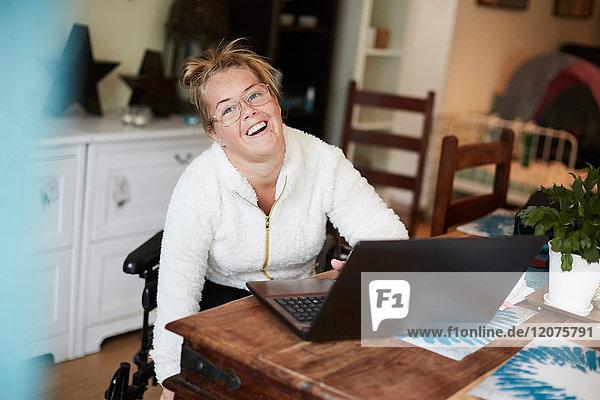 Porträt einer lächelnden behinderten Frau mit Laptop am Tisch im Haus