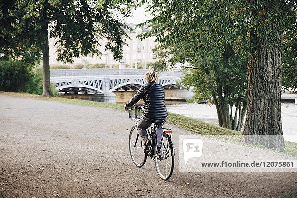 Durchgehende Rückansicht der Seniorin auf dem Fahrrad im Park