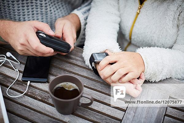 Hochwinkliger Mittelteil von Hausmeisterin und behinderter Frau mit Technologien am Tisch