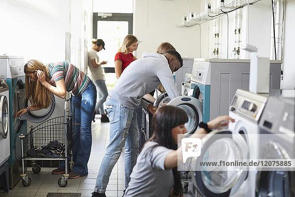 Universitätsstudenten mit Waschmaschinen auf dem Campus Waschsalon