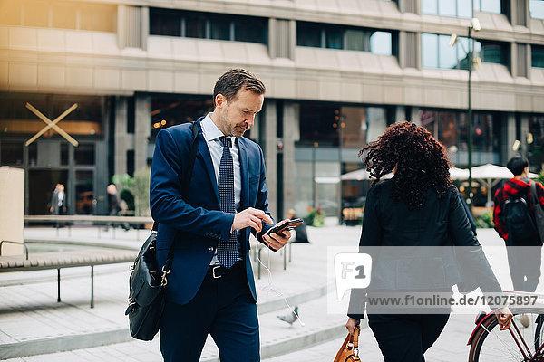 Geschäftsmann mit Smartphone bei einem Spaziergang auf dem Fußweg in der Stadt
