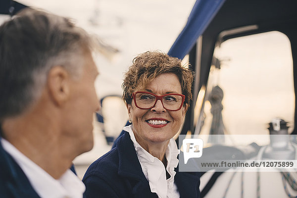 Smiling senior woman looking at man while traveling in yacht