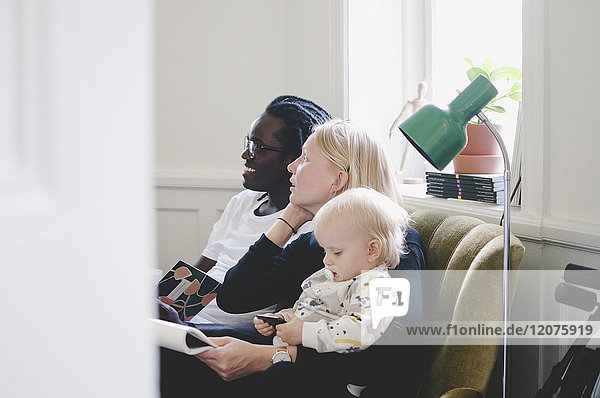 Side view of working mother with baby girl sitting by colleague on sofa in creative office