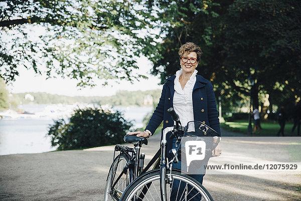 Porträt einer lächelnden Seniorin mit Fahrrad im Park