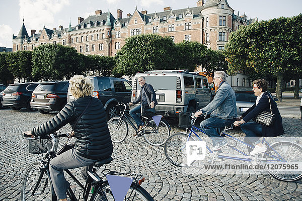 Senior male and female friends riding bicycles on street in city