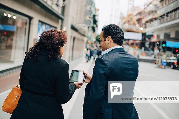 Rückansicht der Geschäftsfrau  die dem Geschäftsmann beim Gehen auf dem Bürgersteig in der Stadt ein digitales Tablett zeigt.
