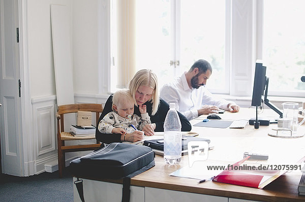 Mittlere erwachsene Geschäftsfrau mit kleinem Mädchen am Tisch im Kreativbüro