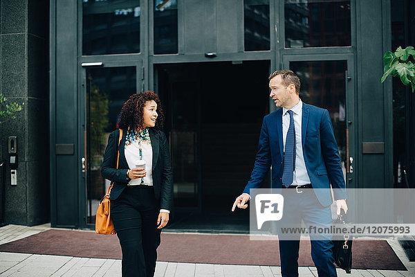 Geschäftsmann und Geschäftsfrau im Gespräch gegen das Bauen in der Stadt