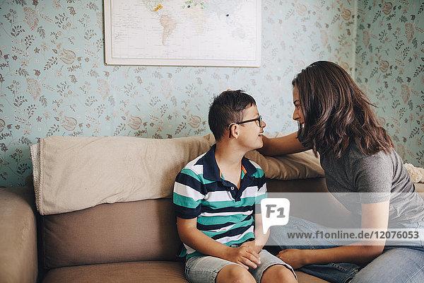 Lächelnde Schwester im Gespräch mit dem behinderten Bruder auf dem Sofa an der Wand sitzend