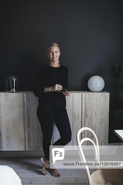 Porträt einer selbstbewussten Geschäftsfrau  die zu Hause am Schrank steht.