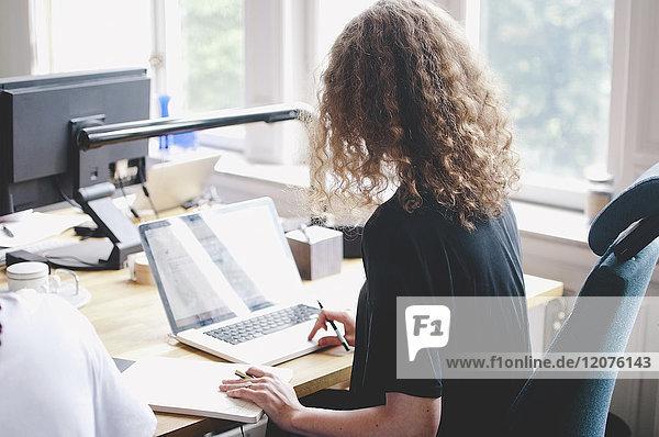 Rückansicht der jungen Geschäftsfrau mit Laptop am Tisch im Kreativbüro