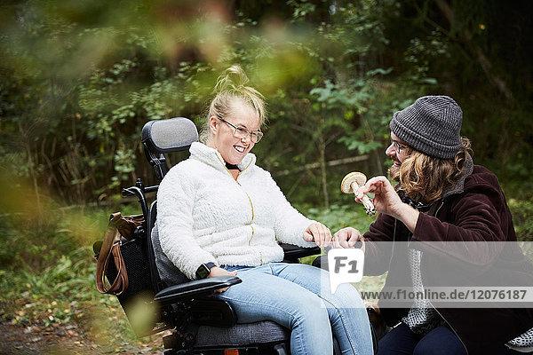 Männlicher Hausmeister zeigt behinderten Frauen im Rollstuhl im Wald den Pilz