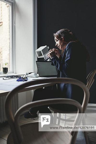 Seitenansicht der Ingenieurin bei der Arbeit an einer tragbaren Festplatte im Home-Office