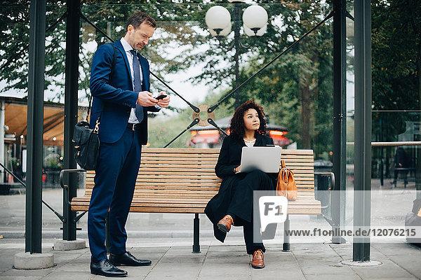 Volle Länge der Geschäftsleute  die Smartphones benutzen  während sie an der Bushaltestelle warten.