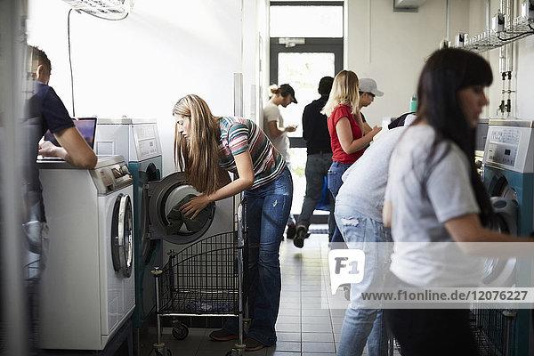 Multiethnische Studenten mit Waschmaschinen im Waschsalon