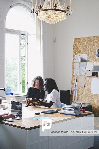 Multiethnische Geschäftsleute diskutieren bei Tisch im Kreativbüro