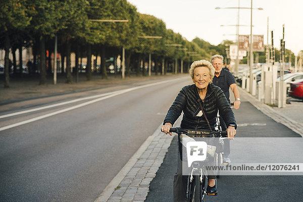 Porträt einer lächelnden Seniorin mit einem Mann  der auf der Stadtstraße Fahrrad fährt