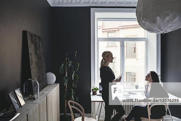 Mitarbeiterinnen diskutieren am Schreibtisch im Home-Office