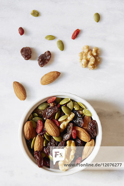 Bowl of nuts and raisins on white background