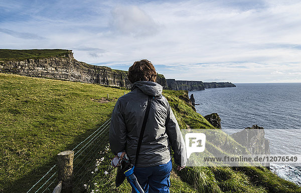 Ireland  County Clare  Woman walking along Cliffs of Moher