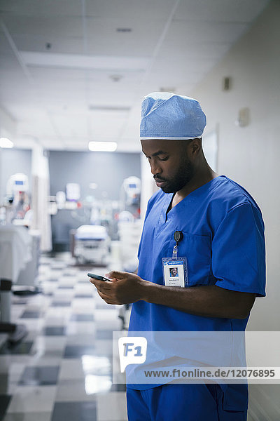 Black nurse texting on cell phone in hospital