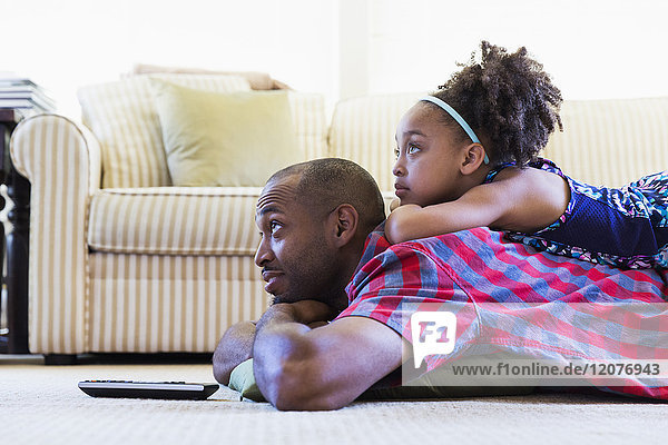 Mixed race father and daughter laying on floor watching television