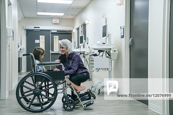 Smiling doctor comforting girl in wheelchair