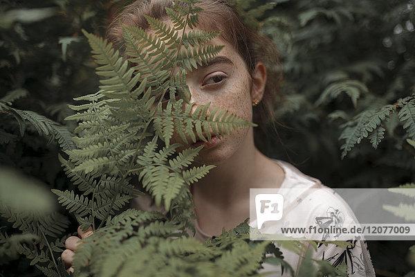 Pensive Caucasian girl behind green leaves